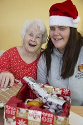 Student nurses at Wrexham Maelor hospital delivering Christmas gifts to patients on  the Bedwen and Onnen long stay rehab wards. Pictured is Ceri Davies delivering a gift to a patient.