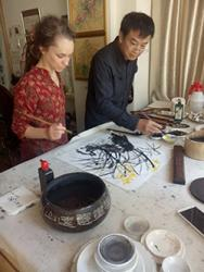 Sophie getting an introduction to Chinese ink paintings from He Rua Hua