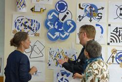 Artistaid Sian Hughes a Lisa Carter yn edrych ar waith credaigol y aelodau gyda Steve Huxton o adran Comissynydd Pobl Hŷn