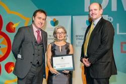 Menna Jones, Chief Executive of Antur Waunfawr, receiving the Award at the Cardiff ceremony with (left) Rhodri Thomas of Cynnal Cymru, hosts for the evening and Mat Roberts of Interserve, sponsors of the Award.