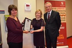 Sarah Horton of the Museums Archives and Libraries Division of the Welsh Government presents the accreditation certificate to Elen Wyn Simpson in the presence of University Vice-Chancellor Prof John G Hughes.