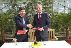 Prof Chen Jin and Prof John G Hughes exchange signed Agreements at Treborth Botanic Garden.