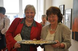 Head of School, Helen Wilcox (left), and Emma Hobbins (right) pictured with a tray of Emma's homemade biscuits at the opening of 'Cataloguing the Other Delights'