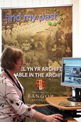 Elen Simpson yn defnyddio adnodd 'Find my past'  sydd bellach ar gael i'w harchwilio yn Archif y Brifysgol.