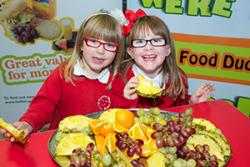 Plant  ysgol yn mwynhau llysiau a ffrwythau fel rhan o weithgareddau Food Dudes.
