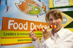 A pupil enjoys a fruit kebab.
