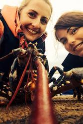 Hannah Finch-Saunders a Robyn Cloake (cynorthwywyr ymchwil) gyda cimwch (Homarus gammarus) yn ystod y prosiect.