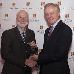 Professor John Witcombe receives the Cultural & Societal Impact Award from Profesor John G Hughes, Vice-Chancellor.