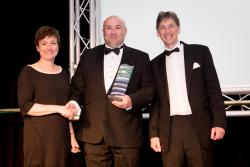 Tony Parry from Delsol being presented with his award by Keynote speaker Rachel Clacher from Moneypenny and Prof. Gareth Griffiths, Bangor University