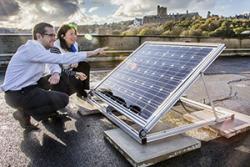 Dr Jeff Kettle a Stevie Scanlan o'r Ysgol Peirianneg Electronig  yn archwilio paneli solar ar ben to'r Ysgol.