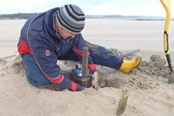 Placing a pressure sensor to measure wave heights across the foreshore in front of the salt marsh at Red Wharf Bay, Ynys Môn.