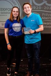 Becca Martin presents choirs conductor Steffan Daffyd with an Award.