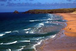 Bathers on Perranporth beach in Cornwall stay in the safe area marked by lifeguards, with large rip currents visible to either side: image credit: Tim Scott