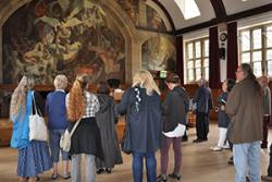 People on a previous tour viewing Ed Povey's mural in the Powis Hall.
