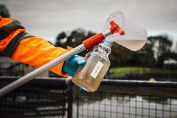 A member of staff collects waste water for monitoring.