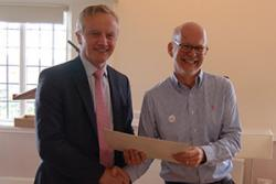 Elwyn Hughes (right) presents the Vice-chancellor with his certificate.