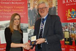 Claire Catherall receiving the Bronze Drapers' medal from Master Draper, Nicholas Bence-Trower
