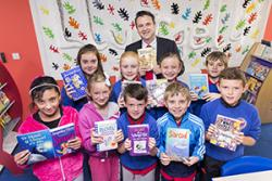 Education Minister Huw Lewis with children from Ysgol yr Hendre, during the official opening of a new community library.