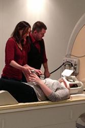 Dr Paul Mullins a Dr Helen Morgan o Ysgol Seicoleg y Brifysgol yn gosod siopiwr yn y sganiwr fMRI.